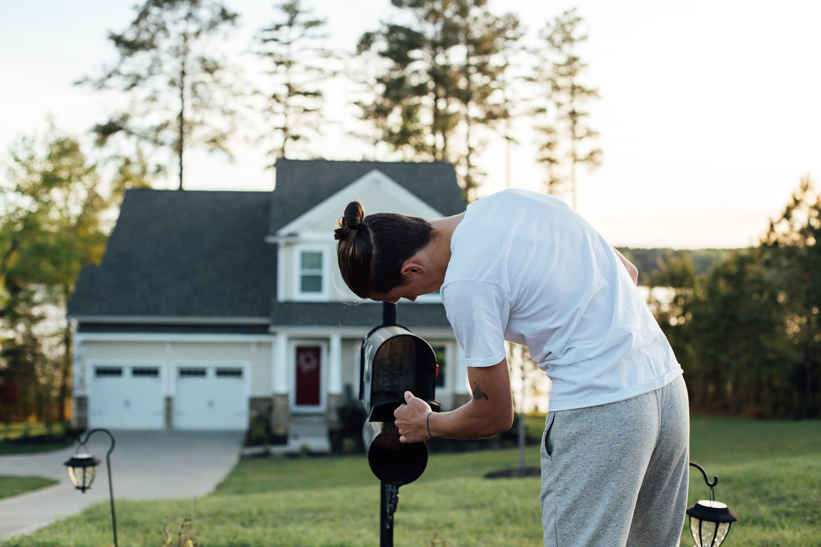 A young man in a white t-shirt checks his mailbox for letters and postcards in front of his house.