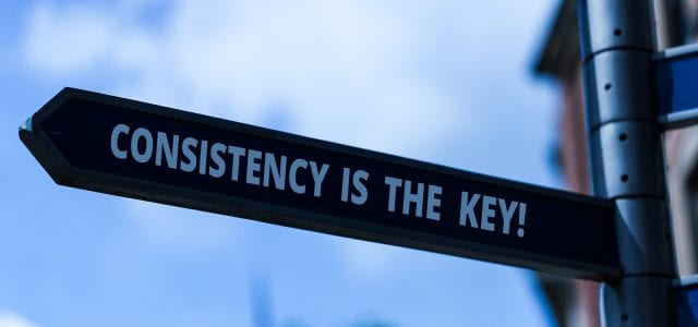 A road sign points to the left and says Consistency is the Key!