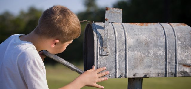 A cute boy, checking the mail in an open mail box. The kid is waiting for the letter, checks the correspondence and looks into the metal mailbox.