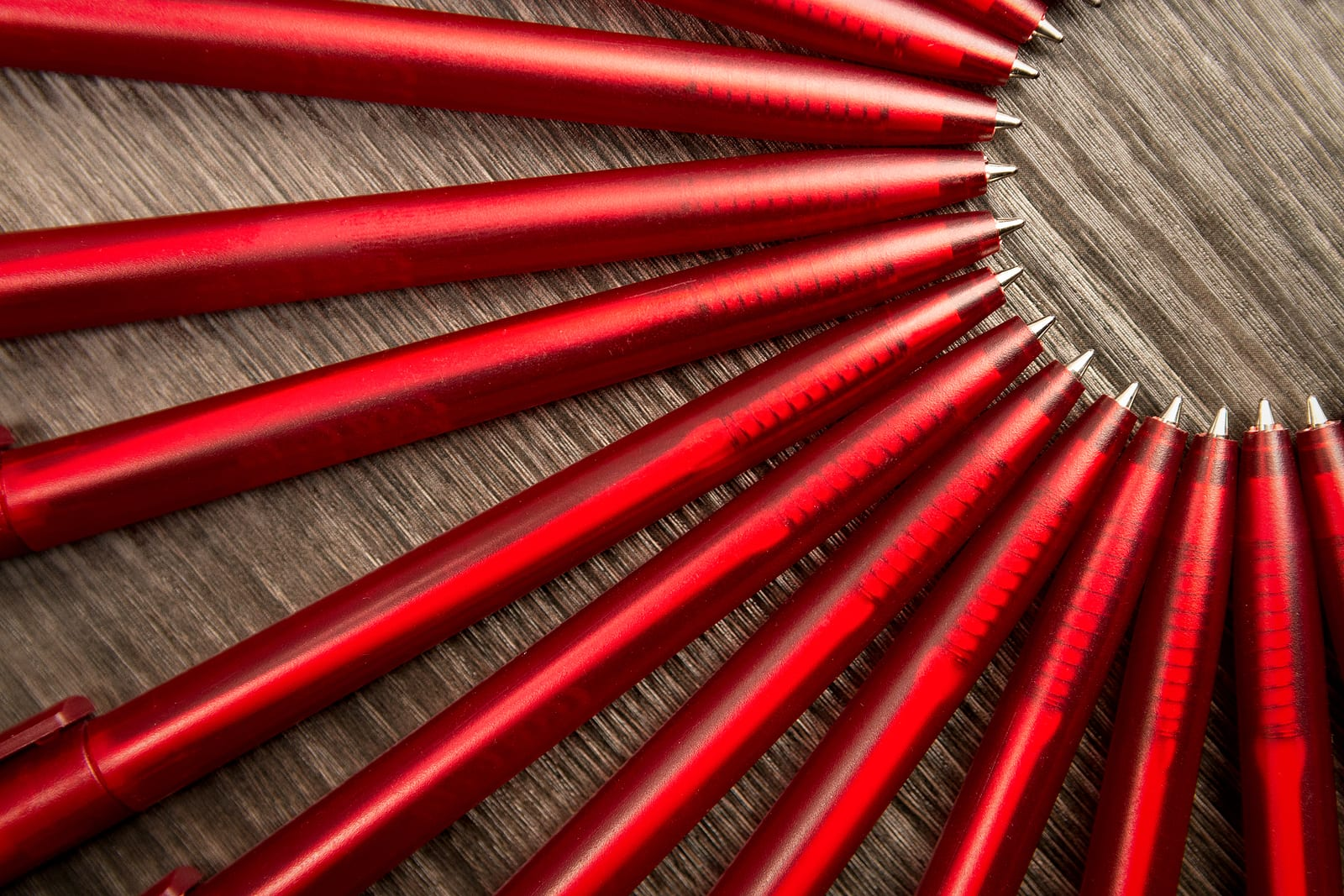 A lot of red pens in a circle on a black wooden background. Concept office or school knowledge day the first of September. great pattern beckground