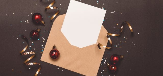 A holiday mailer with confetti and streamers sits on a gray background.
