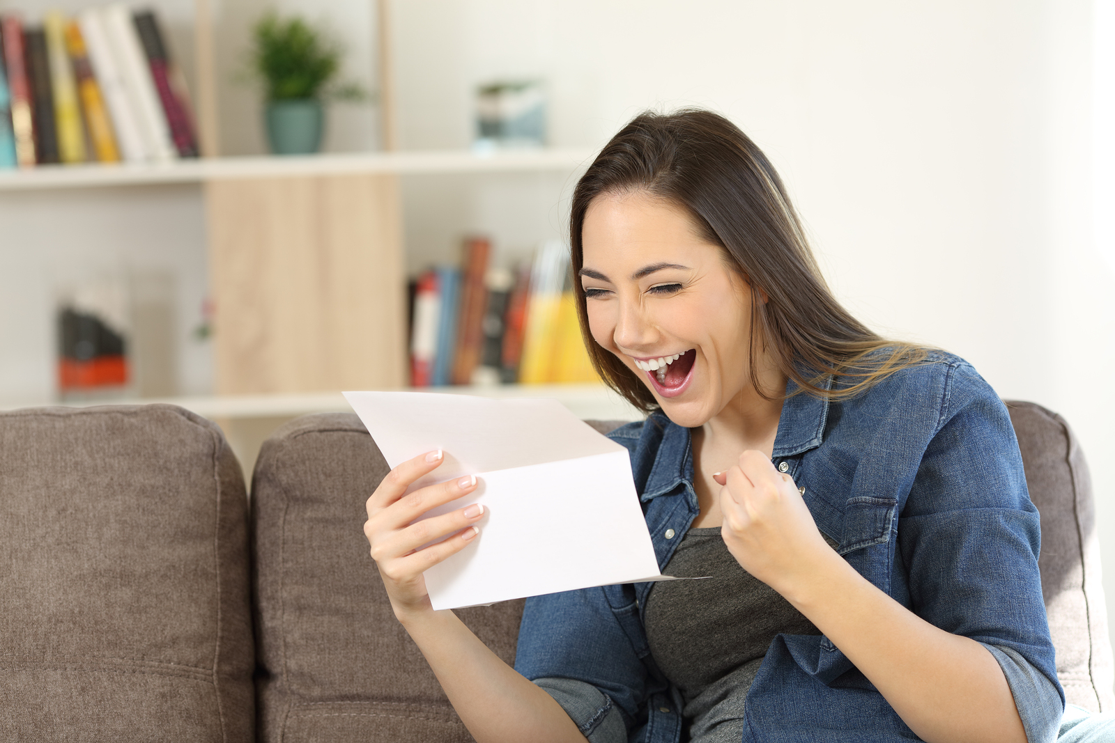 Excited woman reading great news in a letter sitting on a couch in the living room at home