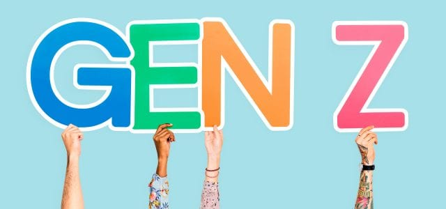 """Four hands hold up letter signs spelling out """"GEN Z."""""""