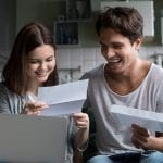 Happy young couple excited by reading good news in paper letter about refund tax money, millennial man and woman glad to receive special offer about cheap deal, direct mail, test results or invitation by mail
