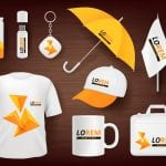 A t-shirt, mug, bag, hat, umbrella, flag, and office supplies all display custom orange logos to promote a business.