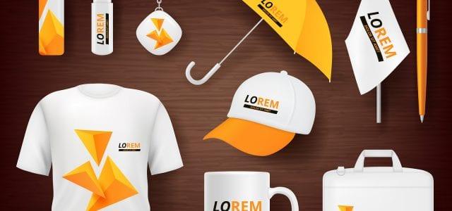 A t-shirt, mug, bag, hat, umbrella, flag, and office supplies all display custom orange logos to promote a business.