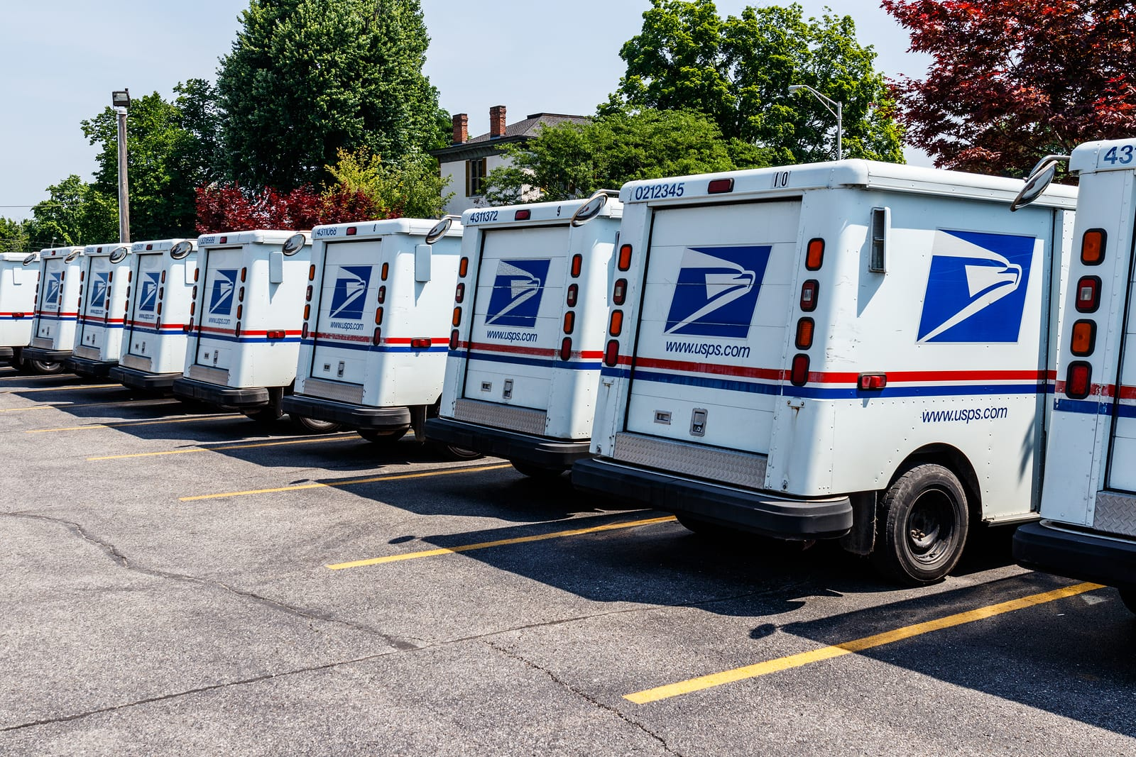 A line of USPS trucks are parked in a parking lot waiting for deliveries.