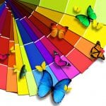 A bright color wheel sits with butterflies of matching colors flying above it.