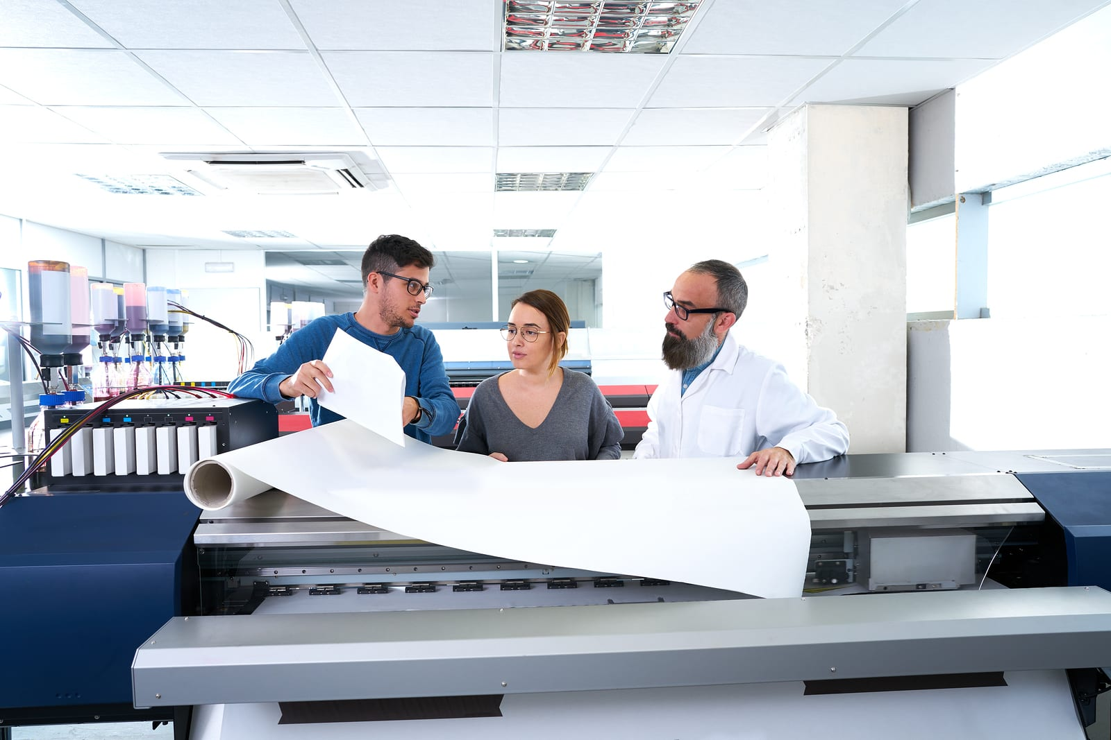 A team of two men and a woman work to isolate a problem with a design in a printing facility.