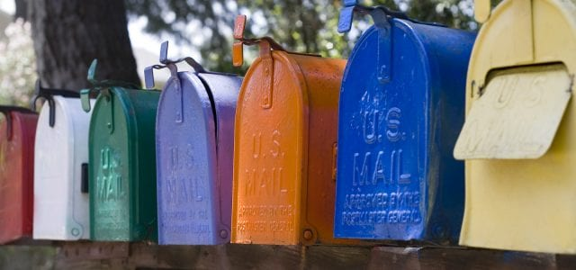 A row of multicolor mail mailboxes all have U.S. Mail stamped on the front.