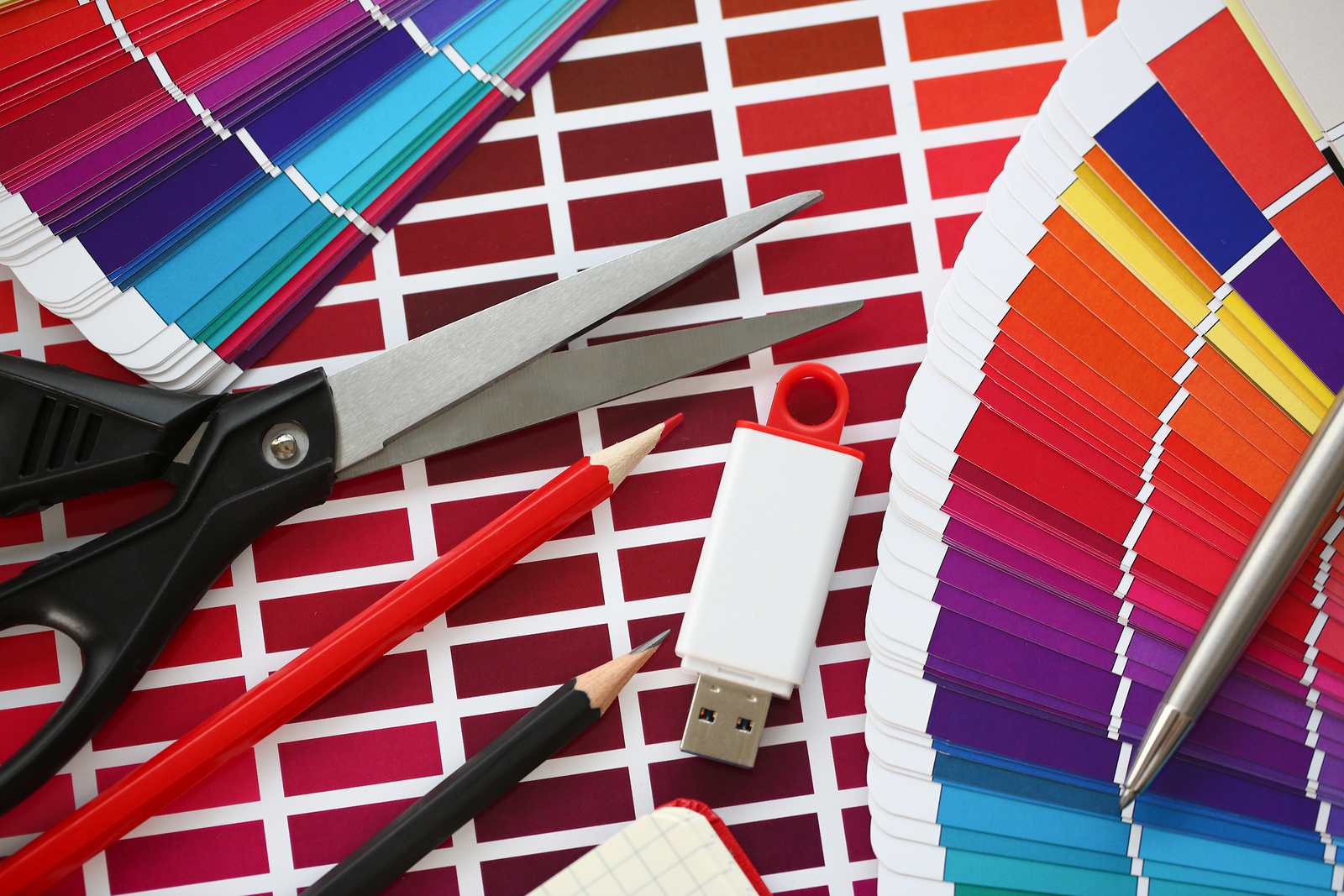 Stationery and USB flash drive on design background. Color print of pantone statistics offset organization gives customer an order products for distribution during promotion concept