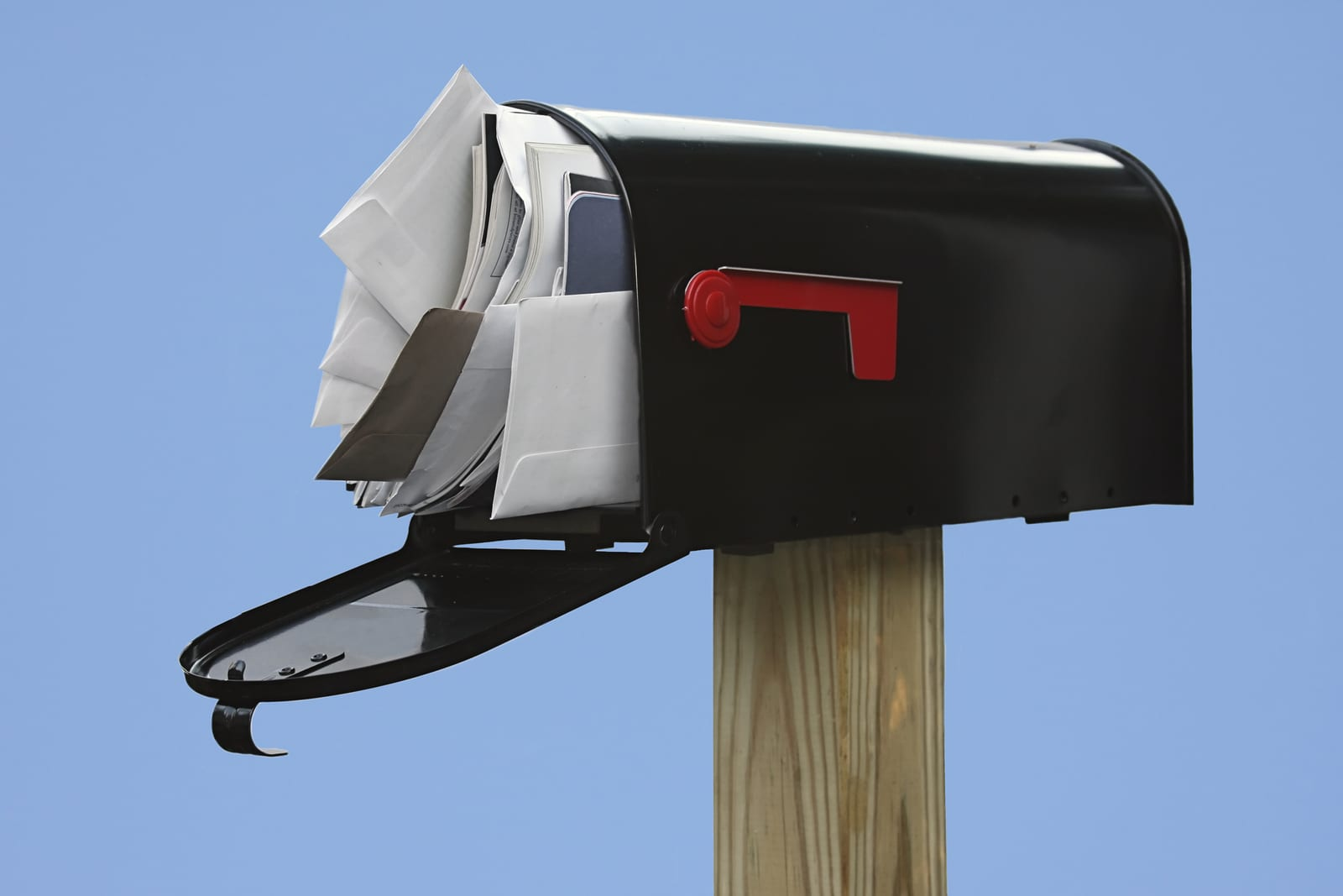 Black Mailbox stuffed with junk mail on a blue background